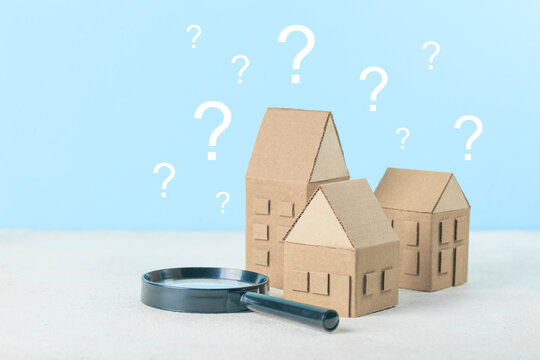 A question on a small house, a magnifying glass examines the building. Assistance in choosing and buying real estate.