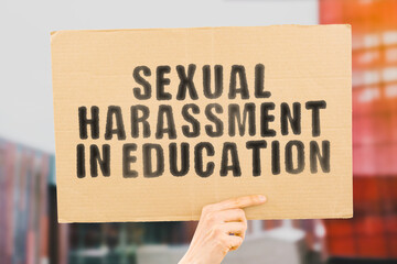 """The phrase """" Sexual harassment in education """" on a banner in men's hand with blurred background.  Homosexuality. Orientation. Gay. Relationship. Communication. Fair"""
