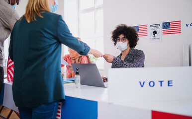People with face mask voting in polling place, usa elections and coronavirus.