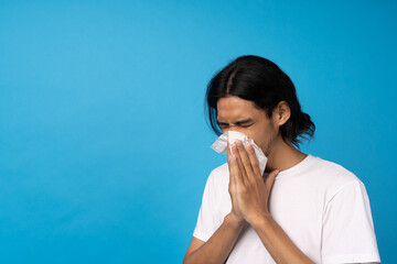 A young man is wiping the toilet paper with water on nose, feeling sick, coughing, sneezing. Concept of sick, influenza