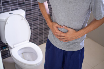 Man abdominal pain and constipation in the bathroom. Concept of health problems, stomach, diarrhea.