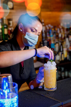 Young bartender girl with mask preparing cocktail on a bar counter. work concept
