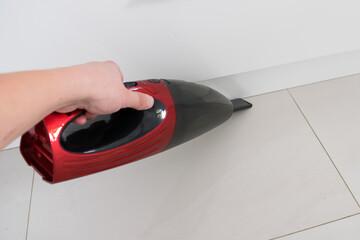 Fototapeta Red car vacuum cleaner, hand holding a car vacuum cleaner, cleaning the floor obraz