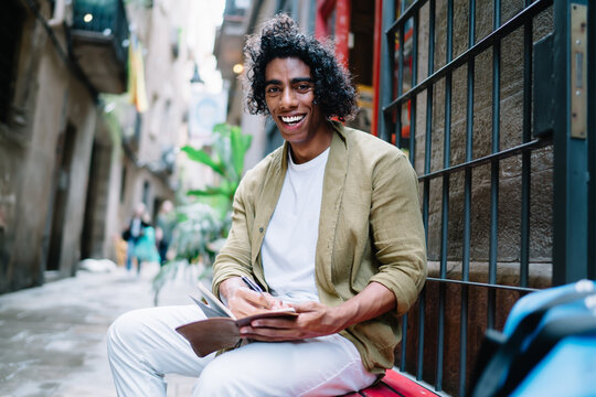 Portrait of cheerful handsome curly male in casual wear enjoying drawing sketches outdoors during free time, smiling young hipster guy 20s creating articles and satisfied with leisure in old city