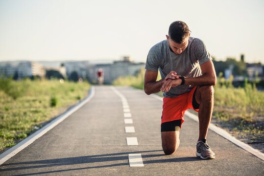 Young handsome sporty jogger taking break from exercising outdoors looking on a smart fitness watch