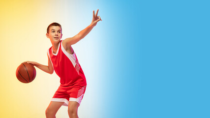 Game. Portrait of young basketball player in uniform on gradient studio background. Teenager confident practicing with ball. Concept of sport, movement, healthy lifestyle, ad, action, motion. Flyer