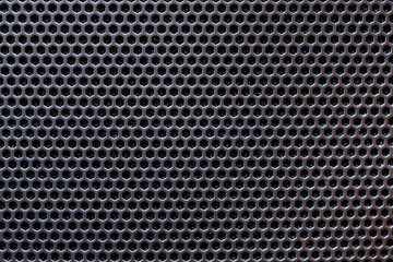 Black metal grate with small holes.