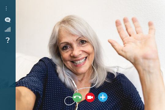 Screen of a happy senior woman waving at camera while making a video call at home - Focus on the old lady face
