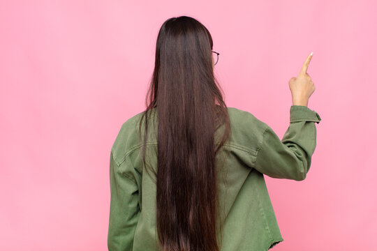 asian young woman standing and pointing to object on copy space, rear view