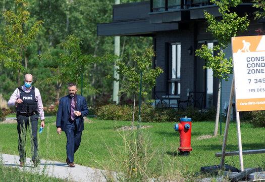 Police investigators walk past a condo building in Longueil