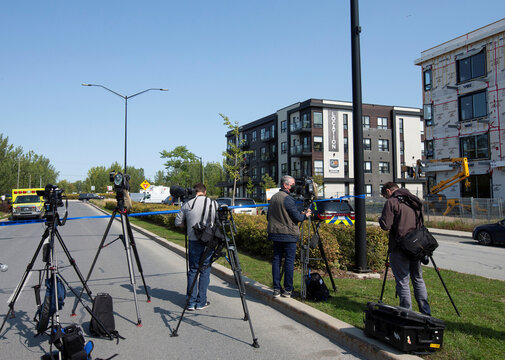 Members of the media wait outside a condo building in Longueil