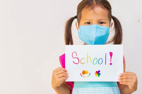 Young student going to school, wearing a mask during covid epidemic. School health and safety.