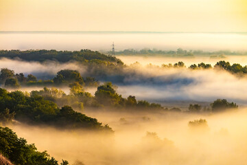 Beautiful panoramic landscape with river valley covered by thick fog in autumn in the early morning. Sunrise. Sun rays shine through the thick fog. Electric power transmission line in fog.
