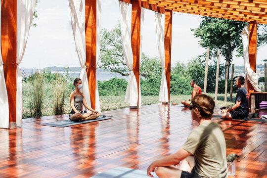 Socially distanced yoga class outdoors on terrace