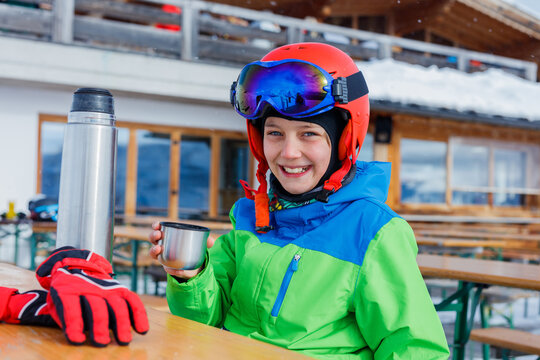 Cute skier boy in a winter ski resort.