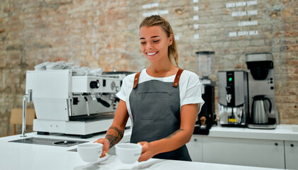 Young attractive female barista stands at the counter in a coffee shop and smiles, serving cups of prepared coffee to a customer.