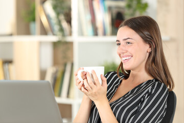 Happy woman drinking coffee looks away at home