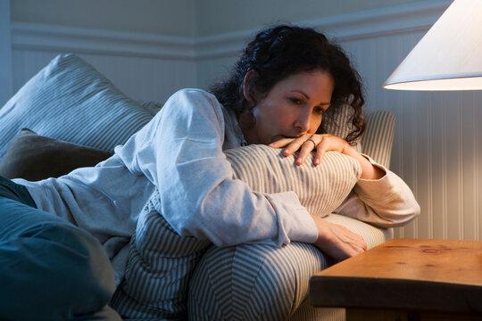 Worried Caucasian woman sitting on sofa