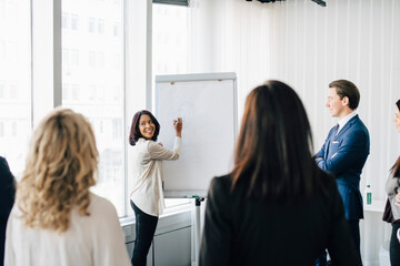 Female entrepreneur talking to colleagues while writing on white board in office seminar