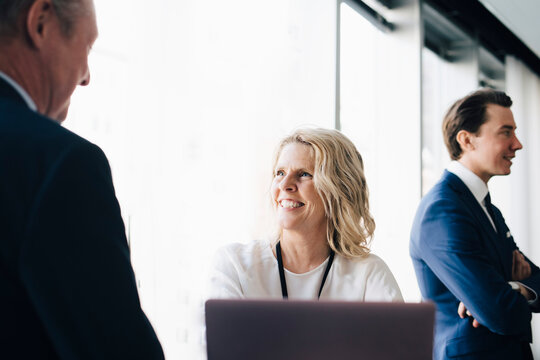 Happy female entrepreneur talking to colleague while coworker standing in background at workplace