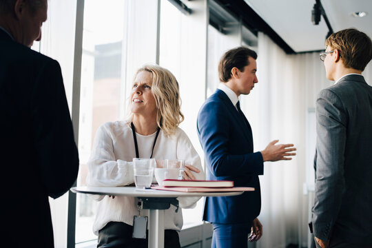 Female entrepreneur talking to colleague while coworker standing in background at workplace