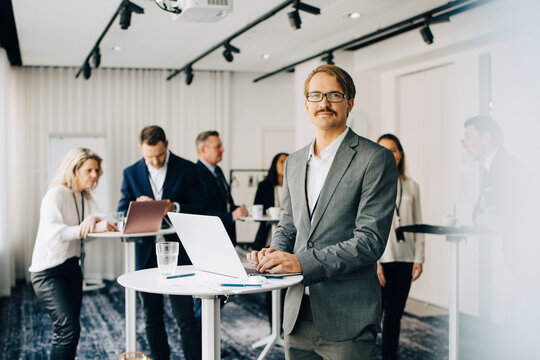 Portrait of businessman working over laptop while standing in office seminar