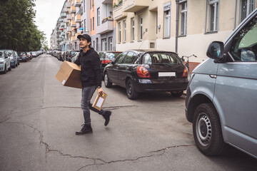 Confident delivery man with package walking on street in city