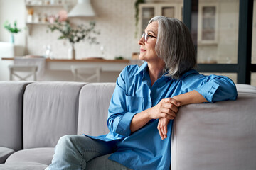 Calm relaxed mature older woman relaxing sitting on couch at home. Peaceful middle aged grey-haired lady resting on sofa in modern living room enjoying lounge and no stress, looking away, thinking. Wall mural