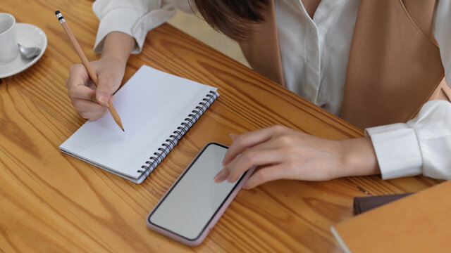 Female looking informations on mock up smartphone and write it down in blank notebook