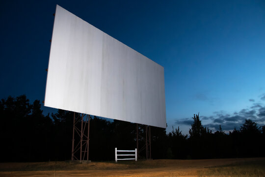 Blank white drive-in movie screen; rural outdoor setting
