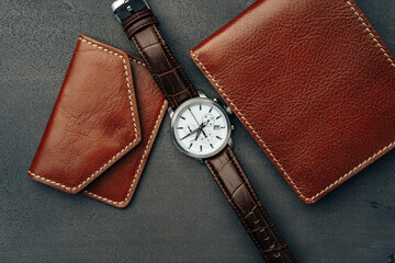 Poster Snelle auto s Male watch and leather wallet on dark grey surface