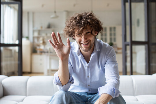 Happy young man blogger influencer waving sit at home speaking looking at camera, webcam view.