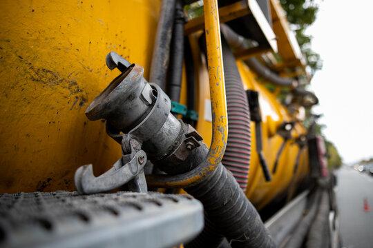 Side view of powerful professional modern yellow sewage sewerage truck working near a house pumping basement canalisation water