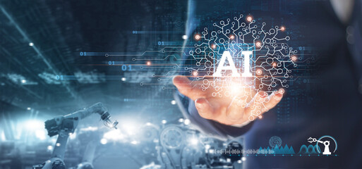 Fototapeta Manager engineer holding brain of (AI) Artificial Intelligence in hand and control automation robot arms machine in intelligent factory industrial. Welding robotics and manufacturing operation.