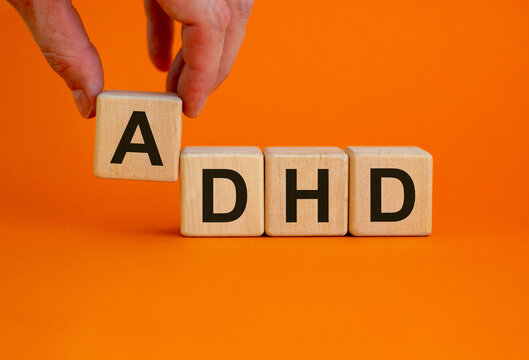 Concept words 'ADHD, Attention Deficit Hyperactivity Disorder' on cubes on a beautiful orange background. Male hand. Copy space.