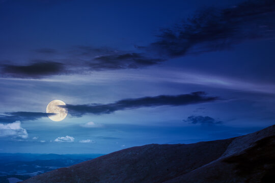 hills and meadows under the blue sky at night. hills and meadows under the blue sky at night. mountain landscape in late summer in full moon light. beautiful scenery in august