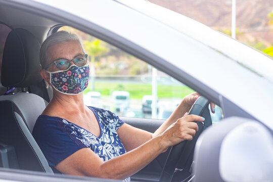 Senior woman wearing a flowered surgical mask because of the covid19 coronavirus ready to drive her gray car looking at camera - concept of active retirees
