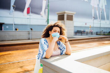Portrait of young woman outdoor wearing mask - Mixed race female in the city protecting from corona virus wearing medical mask - new normal, protection, environment concept