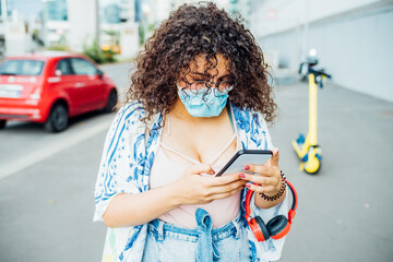 Multiethnic young woman wearing mask using smartphone outdoor - Mixed race young adult female in the city holding smartphone surfing internet