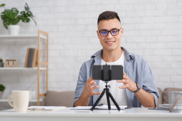 Video recording for modern blog as a remote work or hobby. Happy guy in glasses looks in smartphone camera on tripod, sitting at tae in the living room