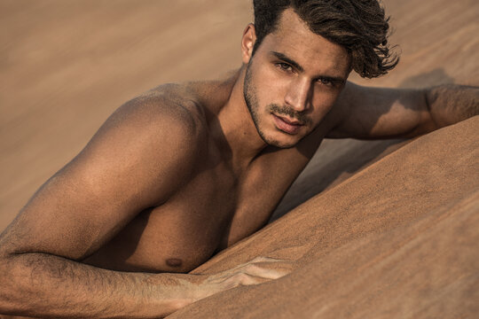 Portrait of sexy handsome shirtless male model on the desert sand dunes.
