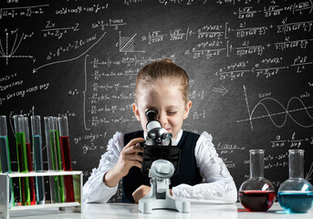 Little girl scientist looking through microscope