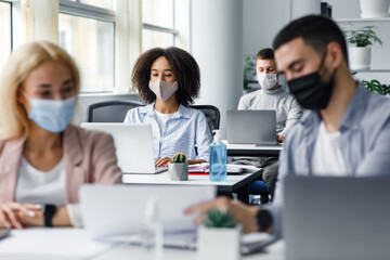 Guy and woman in protective masks are looking at paper, close up, blurred, focus on african american lady typing on laptop at workplace in office interior