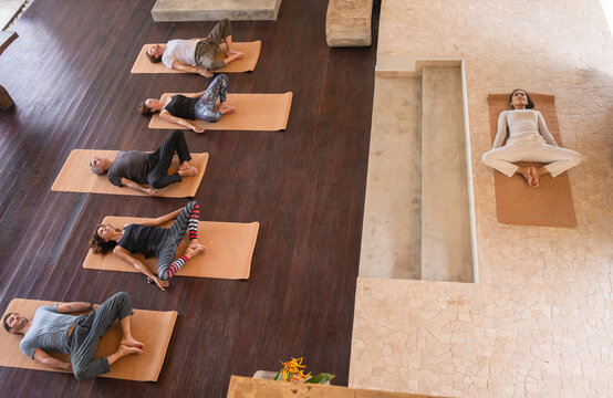 Diverse group of people on wooden floor practicing yoga lying in Reclined Butterfly exercise relaxing after practice. Healthy lifestyle