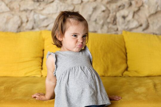 Unhappy toddler girl pouting on yellow sofa