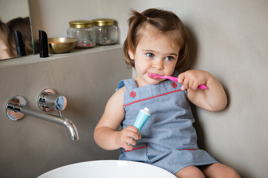 Toddler girl brushing teeth in bathroom