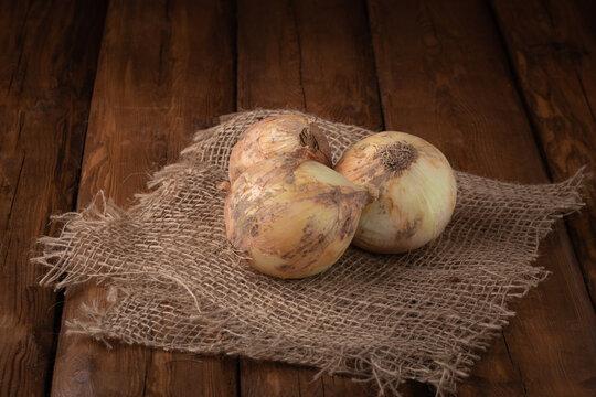 Eco vegetables - fresh yellow onion on wooden background, vegan food