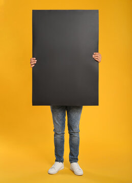 Man holding black blank poster on yellow background. Mockup for design