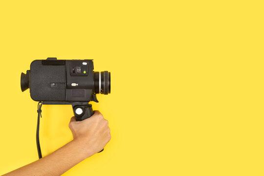 Mano femenina sosteniendo una cámara de película de 8 mm de estilo antiguo sobre un fondo amarillo liso y aislado. Vista de frente. Copy space