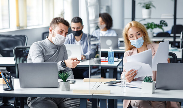 Millennial guy and girl in protective masks discussing and working with documents